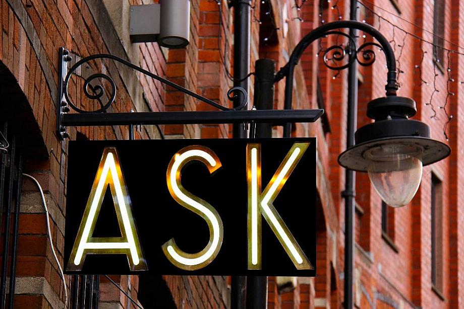 """In großen Buchstaben steht das Wort """"Ask"""" (englisch für fragen) auf einem Schild neben einer Laterne."""