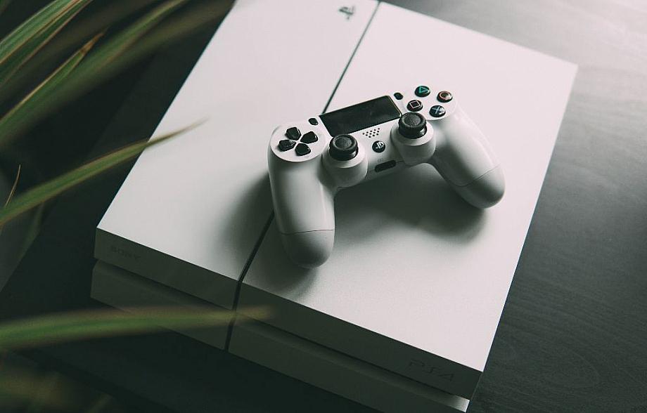 Eine weiße Playstation 4, auf der ein kabelloser Controller liegt.