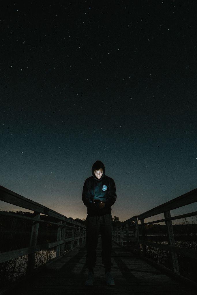 Bei dunkler Nacht steht ein Mann auf einer Brücke und guckt in das hell erleuchtete Disply seines Smartphones.