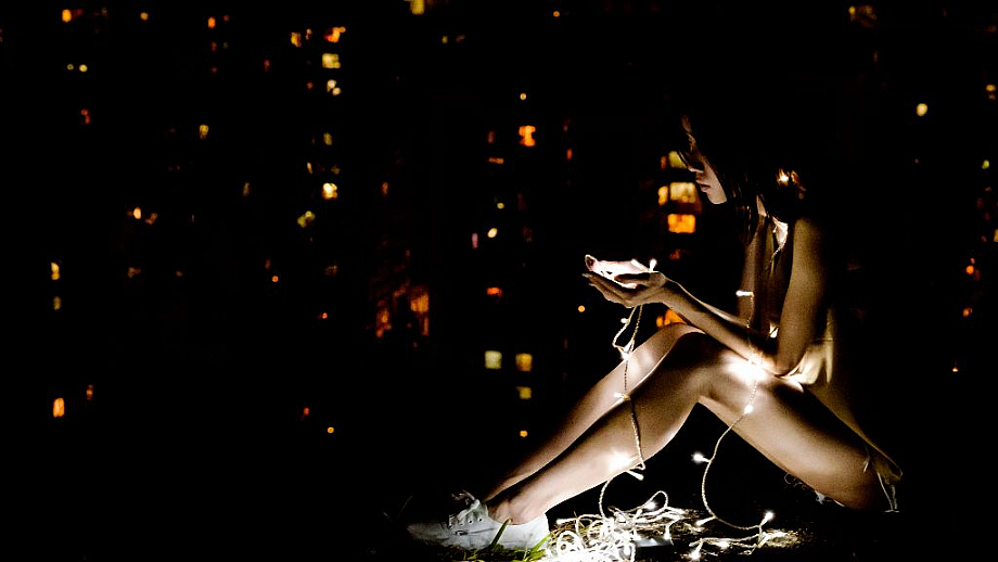 Eine Frau sitzt im Dunkeln und hält eine Lichterkette in den Händen.