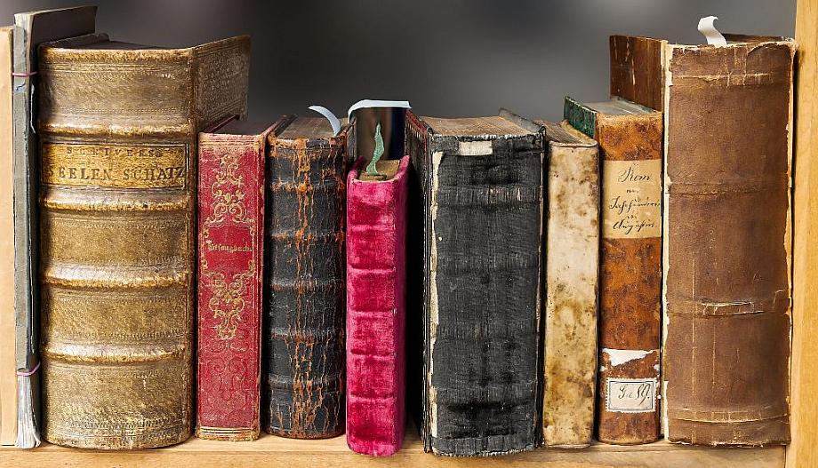 Acht antike Bücher stehen in einem Regal.
