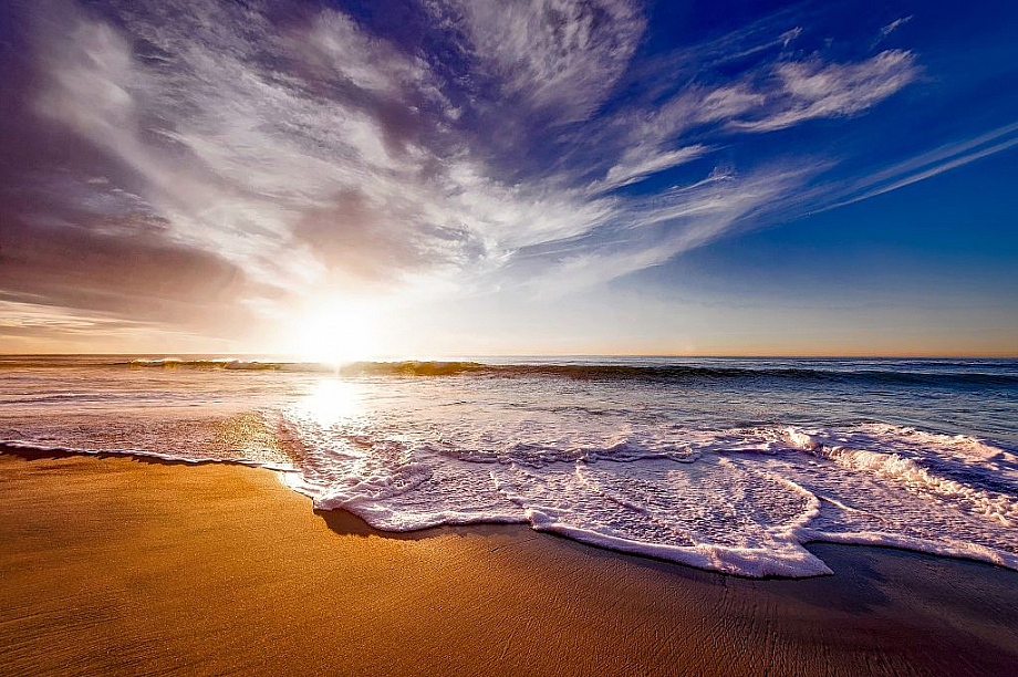 An einem Sandstrand brechen sich die Wellen, während am Horizont die Sonne untergeht.