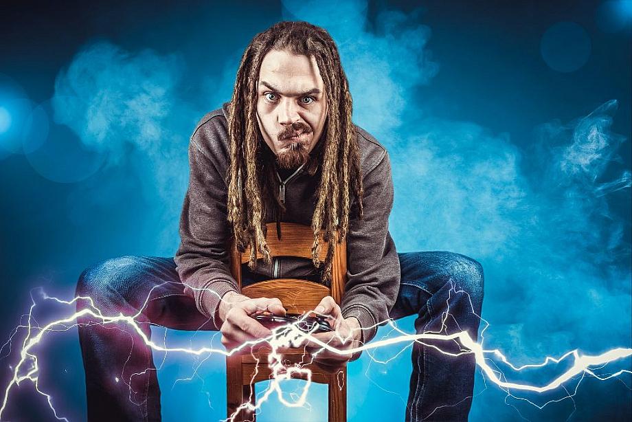Ein Mann mit Dreadlocks sitzt auf einem Hocker, beugt sich nach vorne und hält einen Spiele-Controller in der Hand, aus dem Blitze schließen. Der Gamer guckt hoch konzentriert.