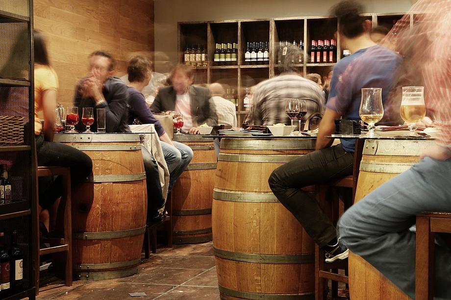 Viele Menschen sitzen in einer Wein-Bar.