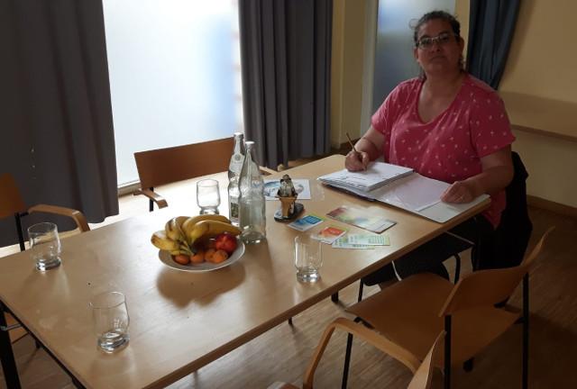 Britta sitzt vor Kopf an einem Gruppentisch und macht sich Notizen in einer dicken Mappe.