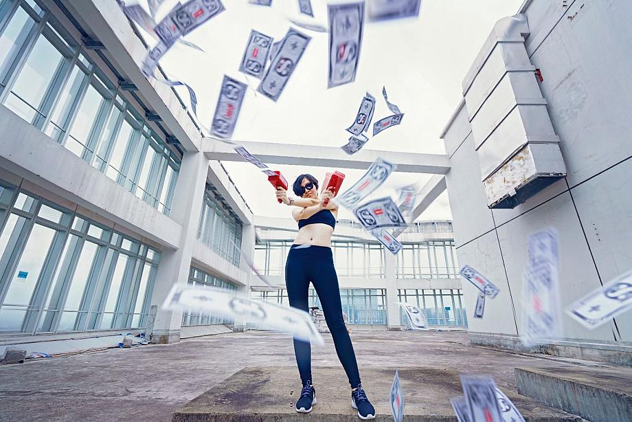 Eine Frau hat zwei Geld-Pistolen in der Hand und feuert Geldscheine durch die Luft.