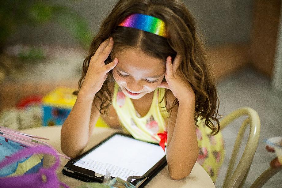 Mädchen sitzt an einem Tisch und schaut konzentriet auf ein Tablet.