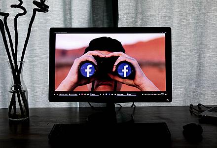 Person guckt durch Fernglas mit Facebook Logos