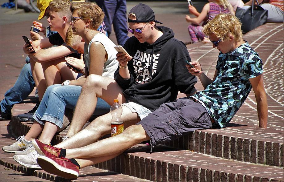 Gruppe von Jugendlichen sitzt zusammen, alle gucken auf ihr Smartphone.