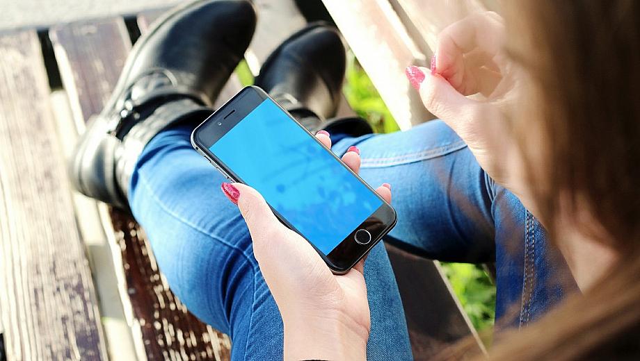 Person sitzt auf einer Bank in der Natur und guckt auf ihr Smartphone.
