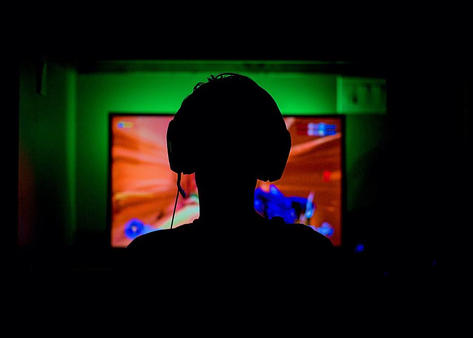 Spieler sitzt vorm Computer und spielt Computerspiel