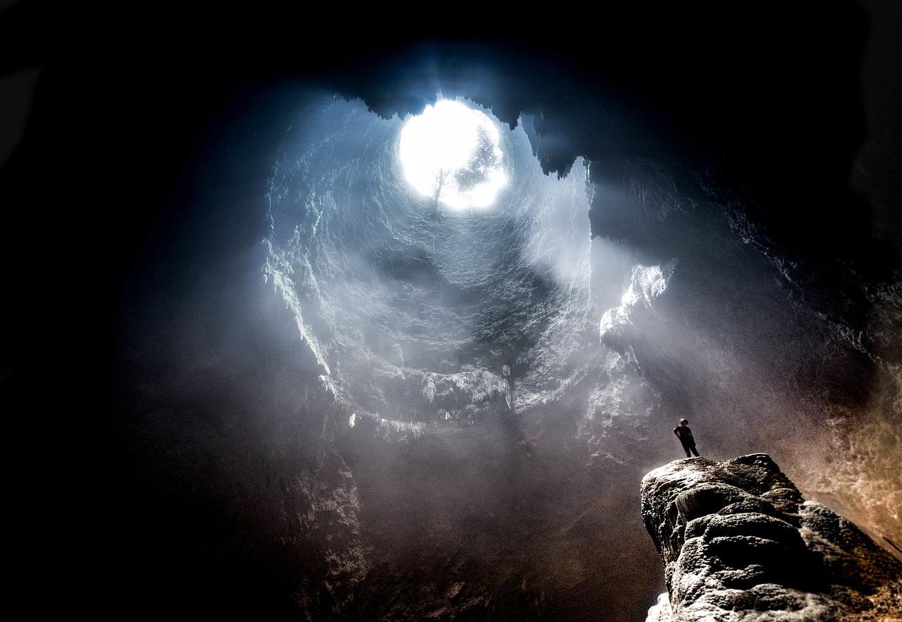 Mensch steht in einer großen Höhle mit einem Loch in der Decke