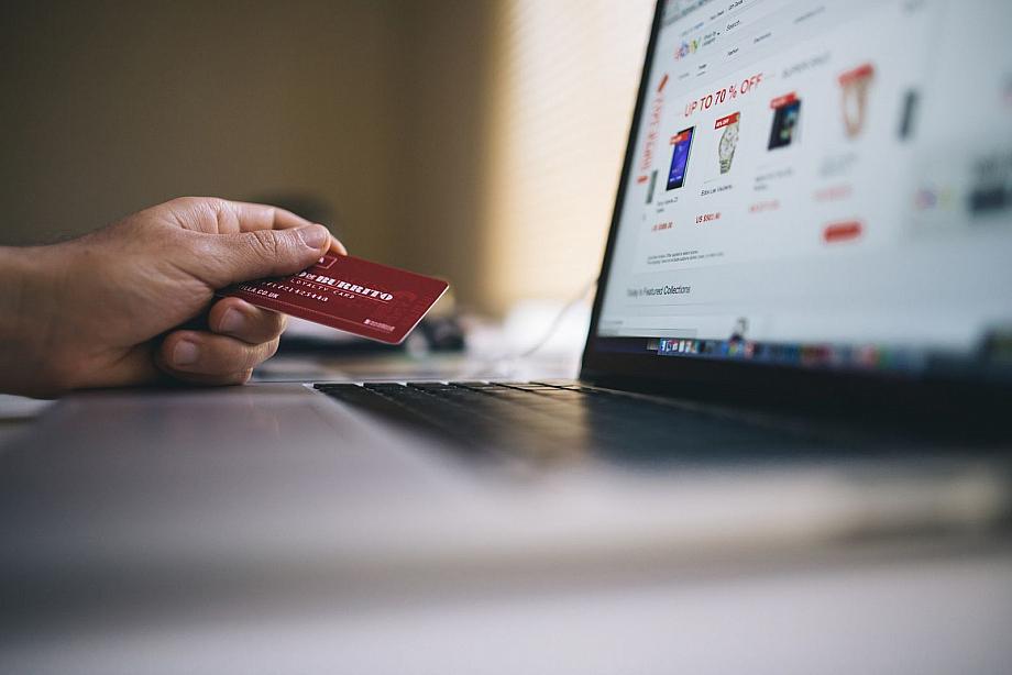 Laptopdisplay mit Online-Shop, daneben eine Kreditkarte