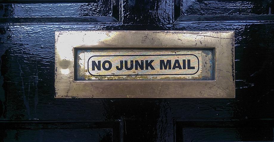 """Briefschlitz in einer Tür. Auf dem Schlitz steht """"No Junk Mail""""."""