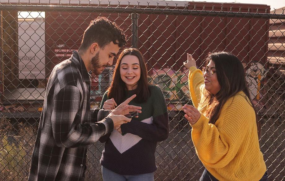 Drei junge Menschen stehen an einem Zaun und gucken auf ein Handy.