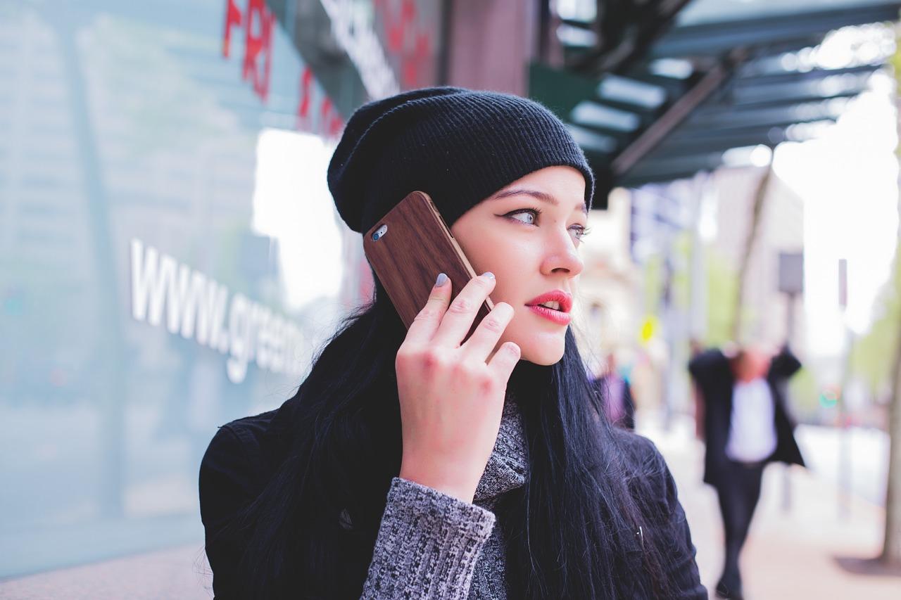 Mensch telefoniert auf der Straße mit dem Handy