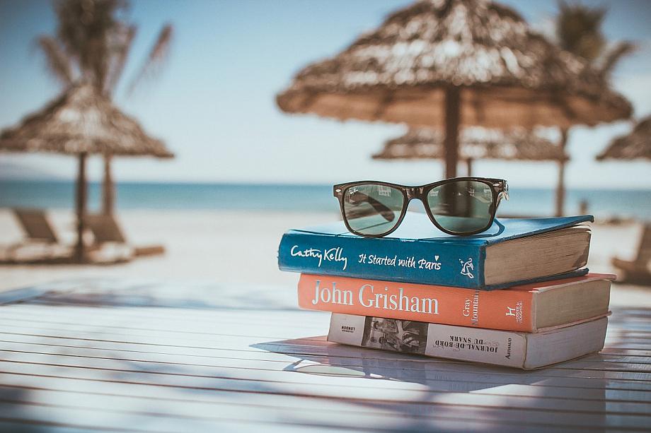 Stapel Bücher und eine Sonnenbrille am Strand