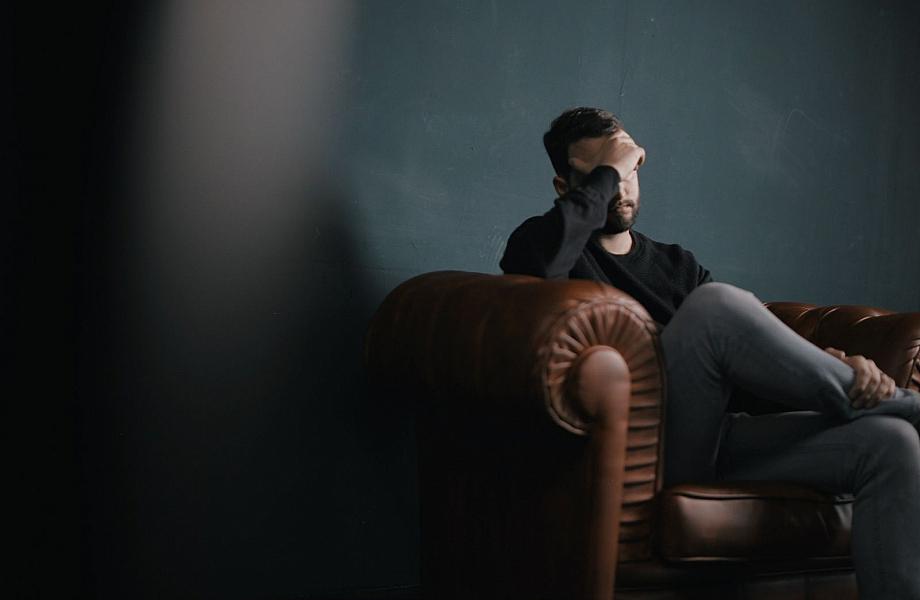 Mensch sitzt auf dem Sofa und packt sich gestresst an den Kopf