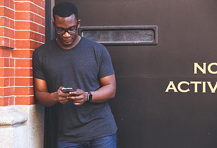 Mensch steht mit Handy vor einer Wand, auf der