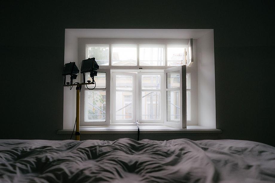 Bett vor einem Fenster, daneben Scheinwerfer.