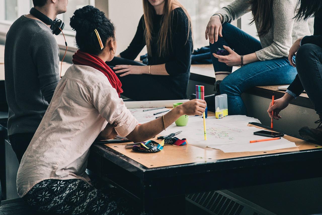 Junge Selbsthilfe: Menschen sitzen um einen Tisch herum und arbeiten.