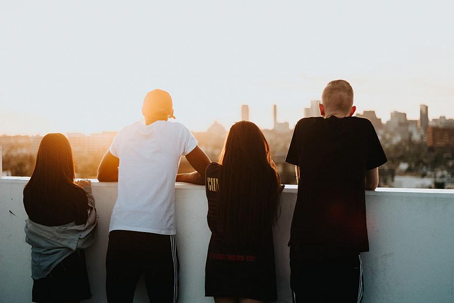 Junge Selbsthilfe: Mehrere Junge Menschen gucken sich von einem hohen Gebäude aus den Sonnenuntergang an.
