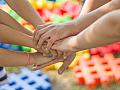 """Junge Selbsthilfe: Mehrere Menschen legen ihre Hände aufeinander nach dem Motto """"Einer für alle, alle für einen""""."""