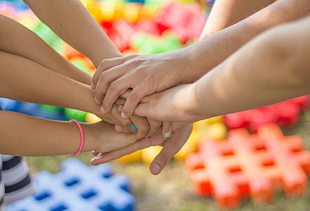 Junge Selbsthilfe: Mehrere Menschen legen ihre Hände aufeinander nach dem Motto