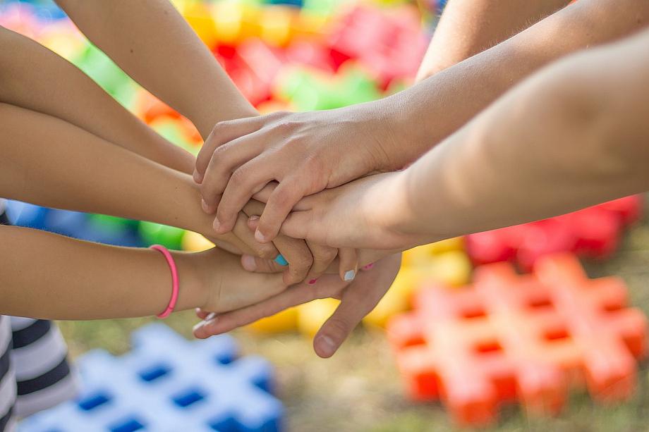 """Mehrere Menschen legen ihre Hände aufeinander nach dem Motto """"Einer für alle, alle für einen""""."""