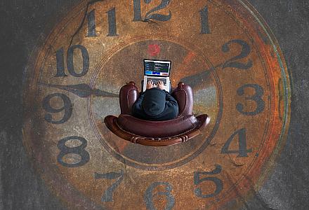 Zeitfresser Pull to Refresh? Mensch sitzt vor einem Laptop, im Hintergrund ist einen große Uhr zu sehen.