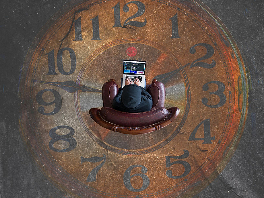 Mensch sitzt vor einem Laptop, im Hintergrund ist einen große Uhr zu sehen.