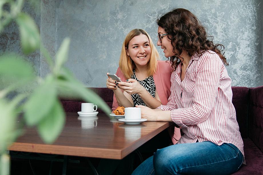 Plauderkreisel: Zwei Menschen sitzen bei einem Kaffee am Tisch und unterhalten sich.