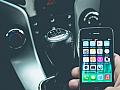 Handy am Steuer: Person hält Smartphone neben der Schaltung.
