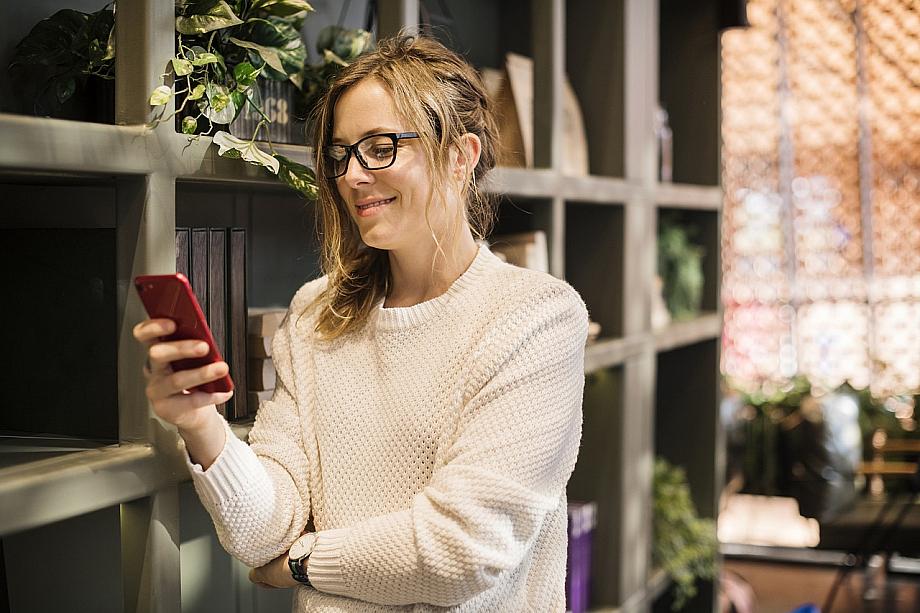 Frau steht vor einem Bücherregal und liest auf ihrem Smartphone.