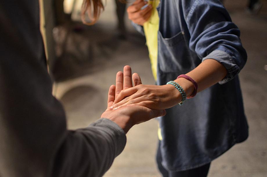 Eine Person reicht einer anderen ihre helfende Hand.