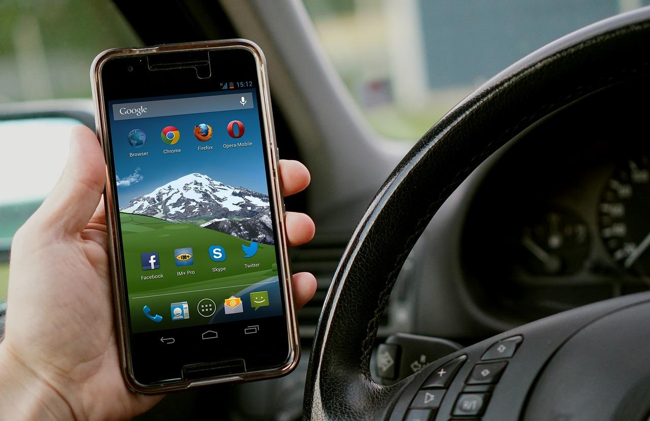 Person hält Handy beim Autofahren in der Hand.