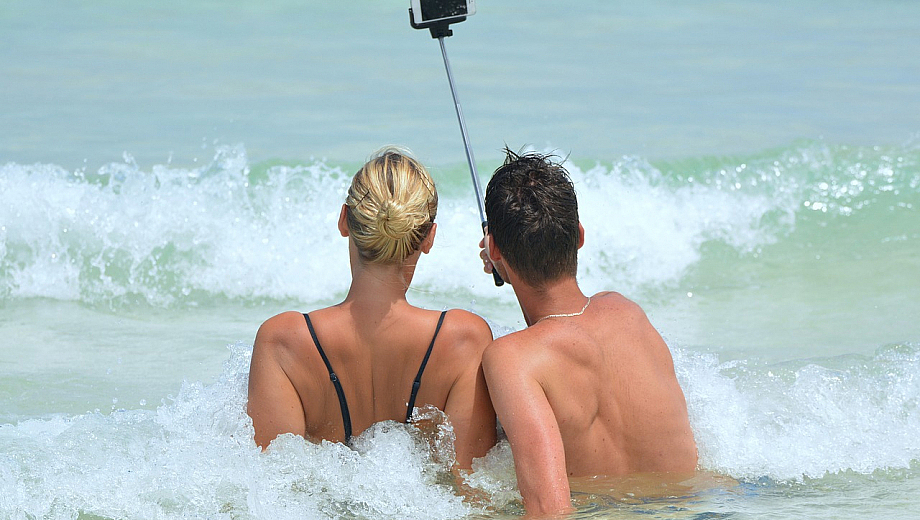 Zwei Menschen sitzen am Strand in den Wellen und machen ein Selfie von sich.