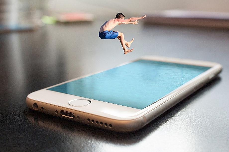 Eine Person hüpft in ein riesen Smartphone, das aussieht wie ein Swimmingpool.