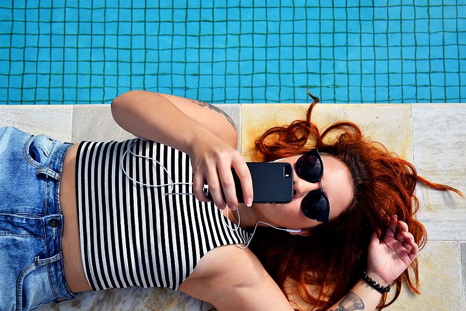 Frau liegt im Urlaub am Pool und hat ihr Smartphone in der Hand.