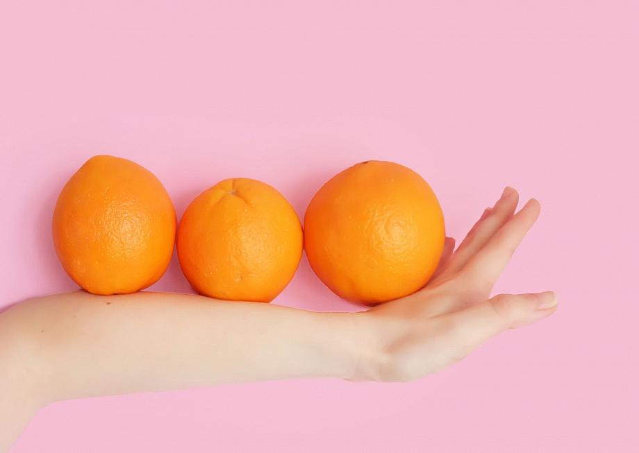 Ein dünner Arm neben drei Orangen.