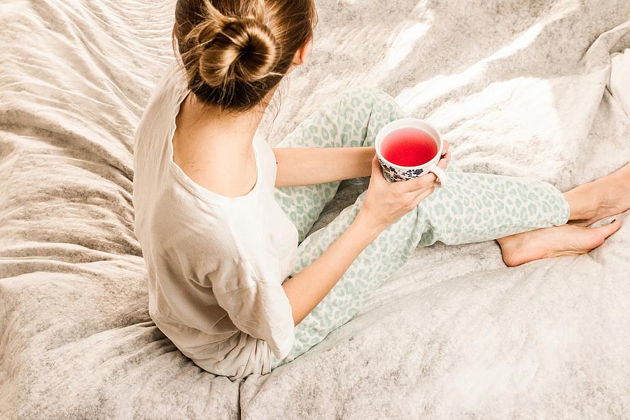 Person trinkt eine Tasse Tee im Bett