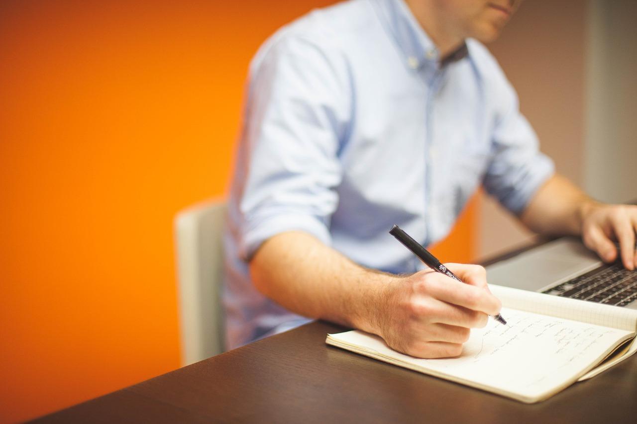 Ein Mann sitzt am Schreibtisch, eine Hand auf der Tastatur, in der anderen Hand einen Stift. Er schreibt etwas in ein Notizheft.