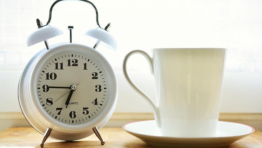 Ein Wecker und eine Tasse stehen auf einem Nachttisch. Das Handy bleibt bei der medienfreien Morgenroutine beiseite.