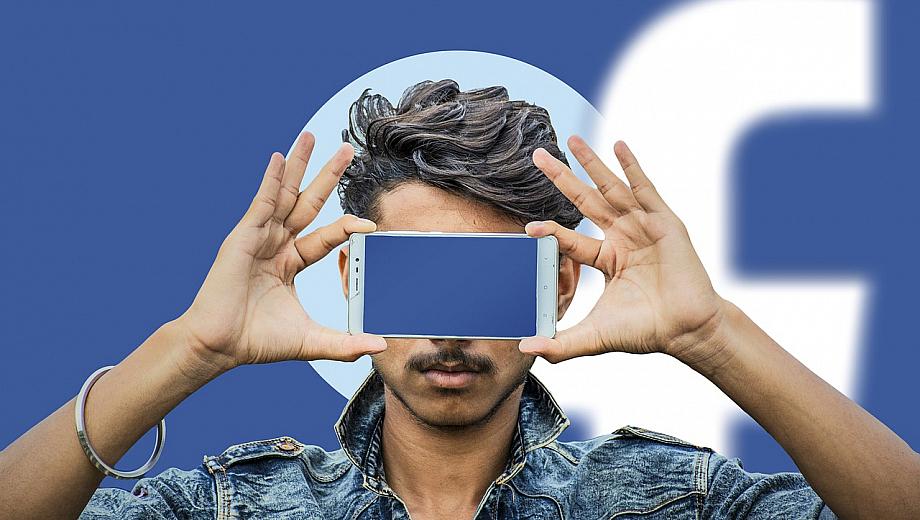 Person hält ein Smartphone vor sein Gesicht. Der Bildschirm leuchtet blau. Im Hintergrund erkennt man das Facebook-Logo.