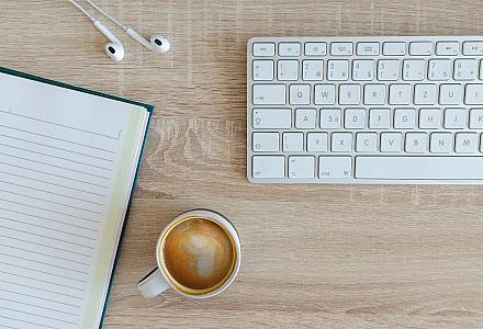 Schreibtisch mit einer Tastatur, einem Notizbuch und einer Tasse Kaffee