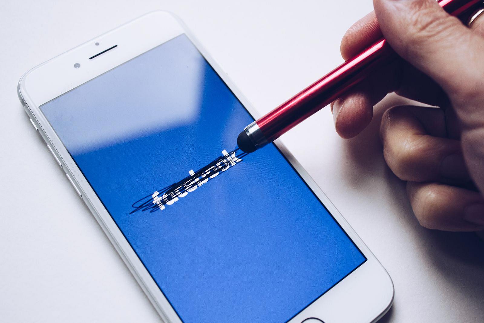 Ein Smartphone zeigt einen blauen Bildschirm mit Facebook-Logo. Mit einem Touch-Stift wurde das Logo durchgestrichen.