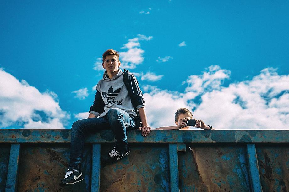 Zwei Jugendliche auf einer hohen Mauer.