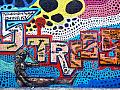 Bunte Graffiti an einer Wand. In der Mitte steht das Wort Stress.