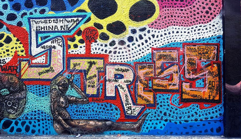 Graffitti an einer Wand, unter anderem das Wort Stress in bunten Großbuchstaben