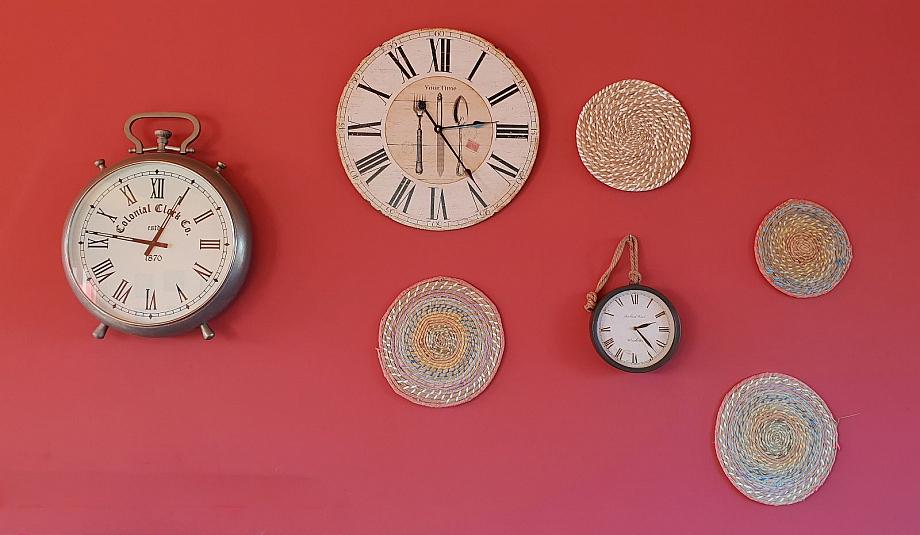 Sieben analoge Uhren an einer roten Wand